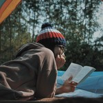 a woman in a hat and glasses reads inside of a tent