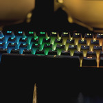 Closeup of a computer keyboard with glowing rainbow keys