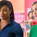 Tiffany Haddish and Rose Byrne sit next to each other at a table, Haddish wears a t-shirt and leather jacket with a high ponytail, while Byrne wears her hair short and bleach blond and holds a coffee cup. They are speaking to each other animatedly.