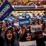 "Crowd of people in an auditorium holding up ""Bernie"" signs"