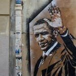Grafitti of Barack Obama, a Black man with short black hair and wearing a suit, raising his hand and nodding on a wall