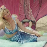 Kirsten Dunst, a white woman with blond hair that's curled at the end, poses in a turquoise mermaid swimsuit in front of a turquoise shell