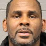 R. Kelly's mugshot, he's standing in front of a cement wall and staring ahead