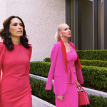 Two wealthy-looking white women wear expensive dresses and walk outside.