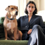 Shelby Lorman sits next to her dog on a green couch. She wears gold earrings and a black suit jacket with striped pants.