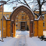 A snow-covered brick archway in front of St. Michael's College School in Toronto. The ground and surrounding trees are also covered with snow.
