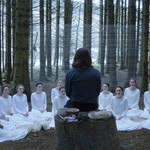 a ring of white-robed women sit in a forest in front of their leader