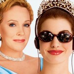 An older white woman with blond hair wears a crown and blue dress and stands beside her granddaughter, a brunette who wears sunglasses and headphones and a crown.
