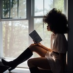 a Black woman with an afro reads a book while sitting on a window sill