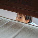 an Asian child peers through the end of a wooden bed