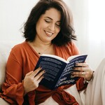 A brown woman with brown hair wears an orange blouse and reads a book on a sofa.