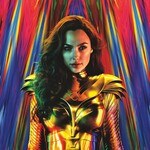 Gal Gadot as Wonder Woman - she wears gold armor and stands against a colorful backdrop