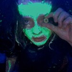 A person covered in a glowing liquid crawls toward the camera. They hold a bright green eye over their eye.