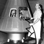 a white woman with blond hair standing in front of a rocket
