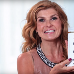 "connie britton holding a shampoo bottle that says ""feminism"""