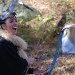 open-mouthed white woman holds bow and arrow