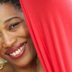 a Black woman with short, brown hair, and wearing a red dress smiles at the camera