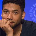 Jussie Smollett rests his chin on his hand against a blue background