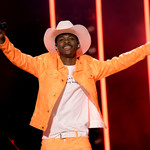 A photo of artist Lil Nas X. Lil Nas X, a black boy, wears a bright outfit and his signature cowboy hat.