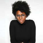 a Black woman with an afro sits in front of a white background