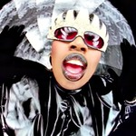 Missy Elliott, a plus-size Black woman dressed in a black trash bag and wearing fingerwaves, in the Supa Dupa Fly video