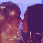 a white teen and an Asian teen face each other lovingly, putting their noses together, and being wrapped in Christmas lights