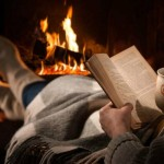 stock photo of person reading by the fireplace