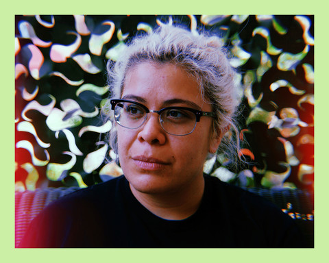 a close-up photo of a Latinx woman with tied back blonde hair, wearing glasses, sitting in front of a patterned green wall and looking off to the side