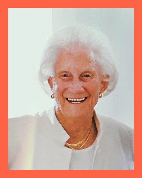 photo of a 91-year-old white woman with bright white hair, smiling whlie wearing a white top and jacket and gold necklaces