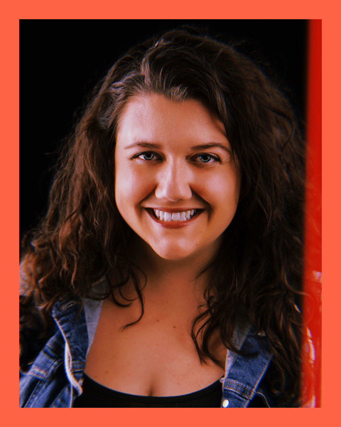 photo of a smiling woman with brown curly hair wearing a black top and denim jacket