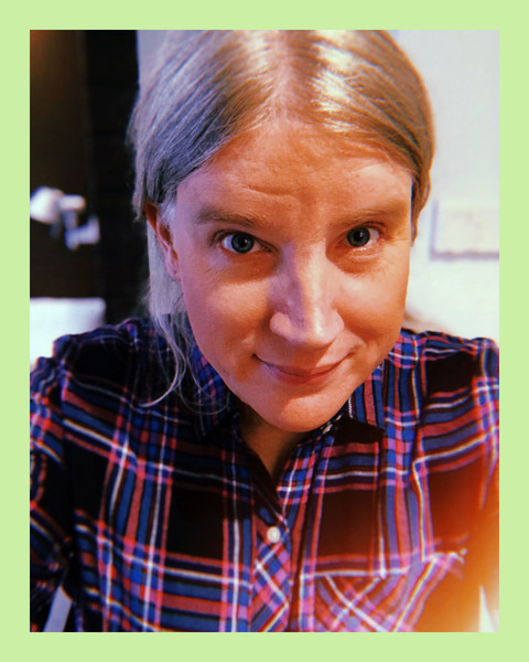 selfie photo of a white woman with light blonde hair, smiling and wearing a blue and red flannel shirt