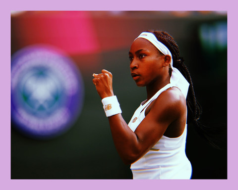 profile photo of tennis player, Coco Gauff, a young Black woman with long black braided hair, wearing a white headband, white top, and white wristband, raising her fist in front of her