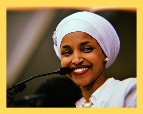 closeup photo of Congresswoman and Somali woman, Ilhan Omar, wearing a white headwrap and white top, looking off to the side and smiling