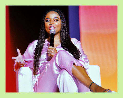 photo of writer, Jemele Hill, a Black woman in a 2-piece silk suit, sitting cross-legged on a stage, speaking to an audience