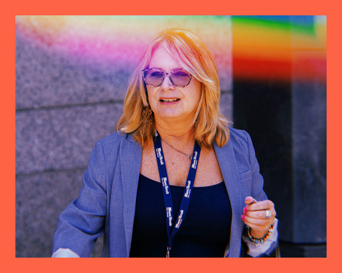 photo of reporter, Julie K Brown, a white woman with short blonde hair wearing a blue blazer and sunglasses, while exiting a building