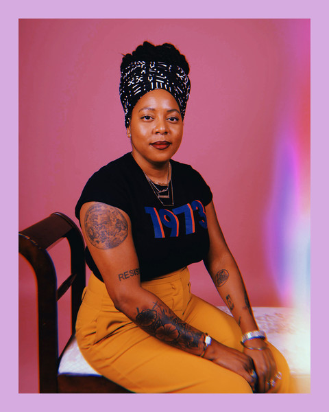 "photo of a tattooed Black woman sitting on a decorative bench wearing a patterned head wrap, yellow pants, and black t-shirt with the numbers ""1973"""
