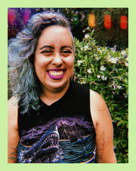photo of a brown woman and activist, Lea Lakshimi Piepzna-Samarasinha, who has curly blue hair and purple lipstic, standing outside smiling while wearing a sleeveless black top with a shark graphic