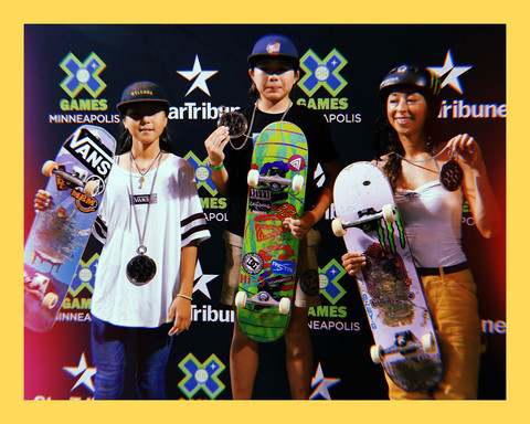 photo of X Games winners, Lizzie Armanto, Cocona Hiraki, and Misugu Okamoto, a young Finnish-American woman and two young Japanese women, standing on podiums holiding their skateboards and medals
