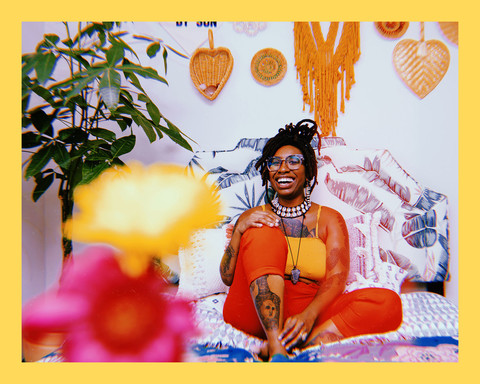 photo of queer illustrator and designer, Loveis Wise, a Black woman with locs in an updo, sitting on her colorful patterned bed smiling, wearing a yellow top and red pants