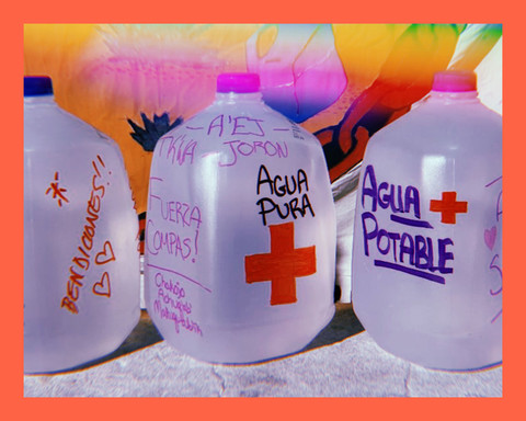 photo of three gallon jugs of water with encouraging words of solidarity for migrants, written by volunteers from the No More Deaths organization