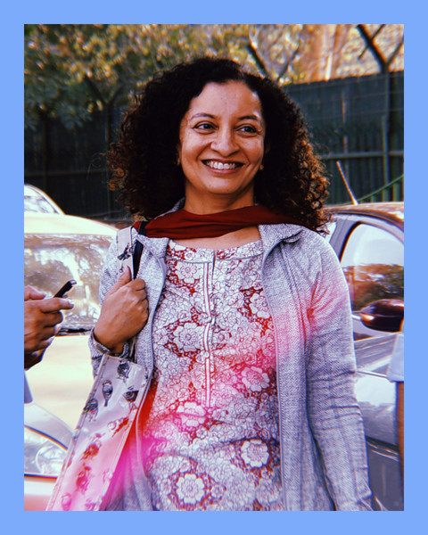 photo of journalist Priya Ramani, a brown woman standing outside, wearing a patterned shirt, a grey longsleeved top, and a red scarf while carrying a bag, looking off to the side and smiling
