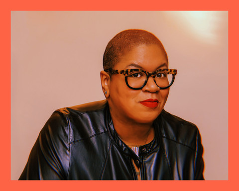 closeup photo of author Samantha Irby, a Black woman with short dark hair, wearing glasses, a red lip, and leather jacket, smiling.