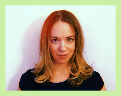 selfie photo of author Sarah Kendzior, a white woman with blonde hair, wearing a blue shirt and smiling in front of a white wall