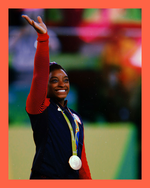 photo of Olympian, Simone Biles, a Black woman wearing a red and blue tracksuit with a gold medal around her neck, while waving to the crowd and smiling