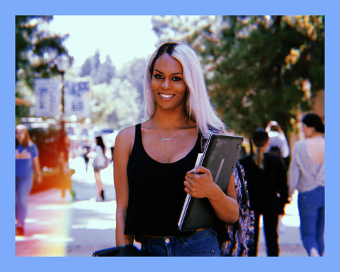photo of a Black woman with long platinum white hair, standing on a campus wearing silver hoop earrings, a black tank top and jeans, while smiling and holding her laptop