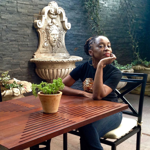 Photo of Bassey Ikpi sitting at an outdoor table