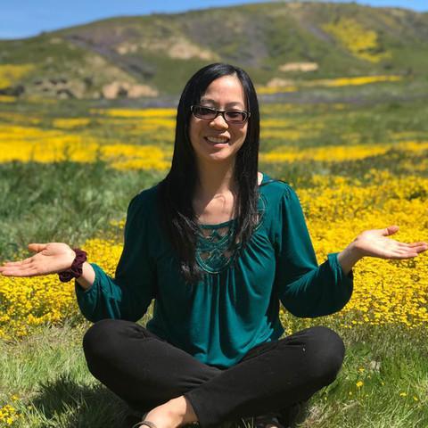 Emily Wu Truong sitting crosslegged in a grassy field