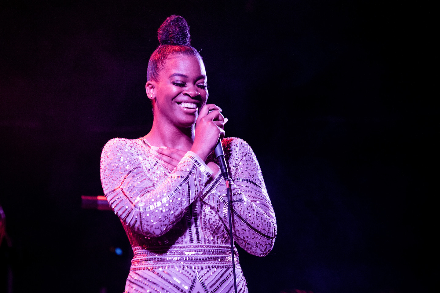 Ari Lennox, a brownskinned Black woman with a black bun, smiles on stage as she performs