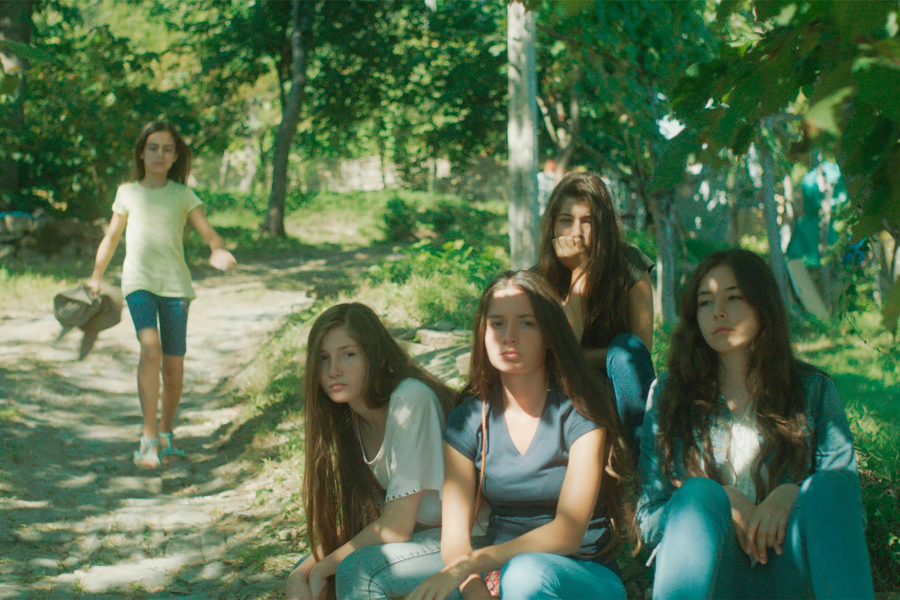 Five Turkish sisters sit under a tree in the film Mustang