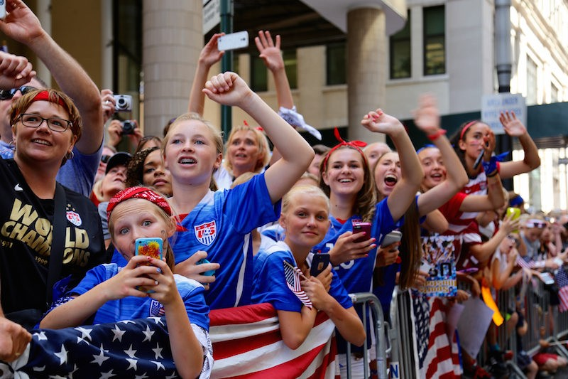 fans cheering on the soccer team in an nyc parade